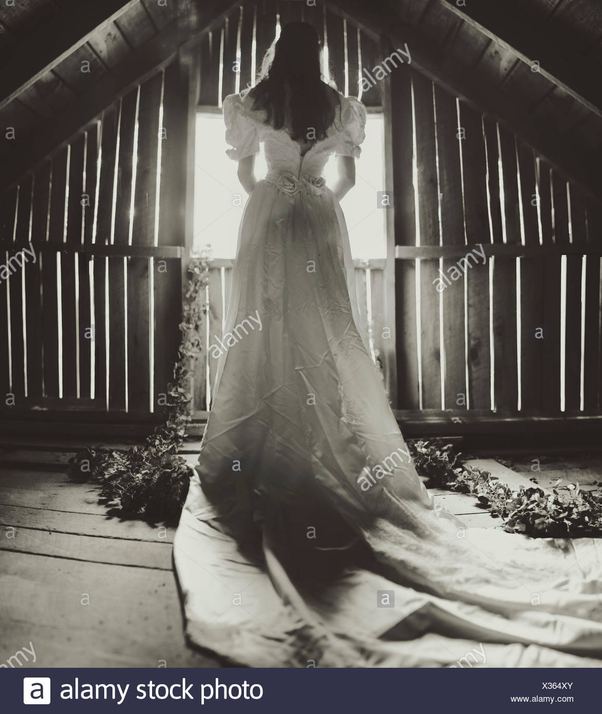 Rear view of young woman in wedding dress on attic - Stock Image