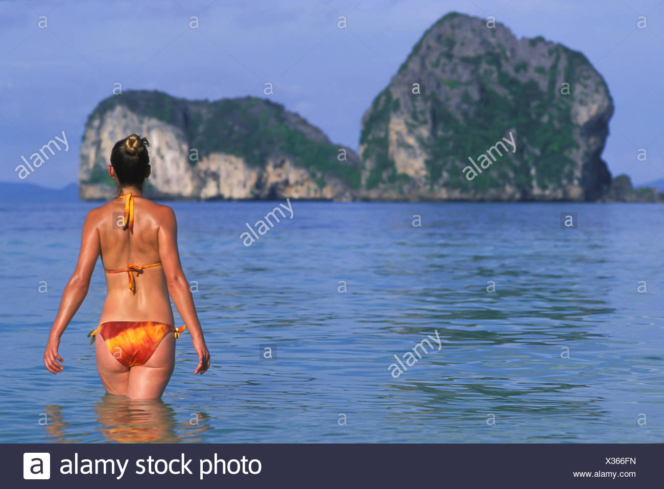 A Woman Tourist Wearing A Bikini Enjoys The Sunshine On The Tropical Island Of Koh Ngai Or Ko Ngai Near Trang; Koh Ngai Thailand - Stock Image