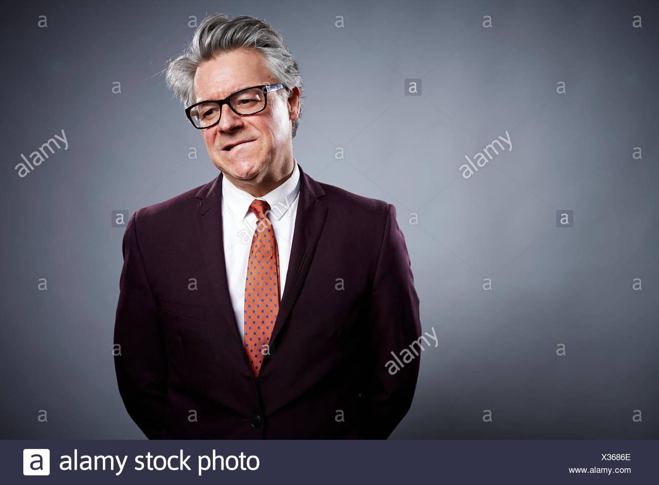 Studio portrait of businessman biting his lip - Stock Image