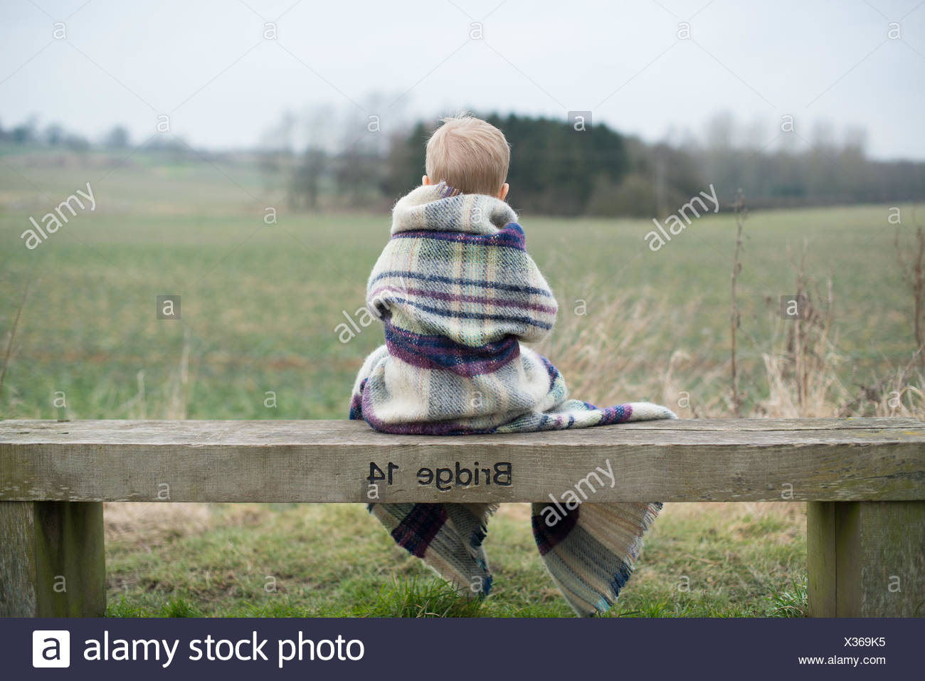 Rear view of a boy sitting on bench, wrapped in warm blanket - Stock Image