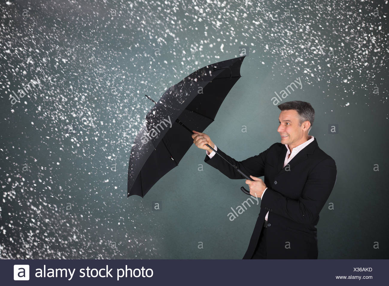 Businessman With An Umbrella In Snow - Stock Image