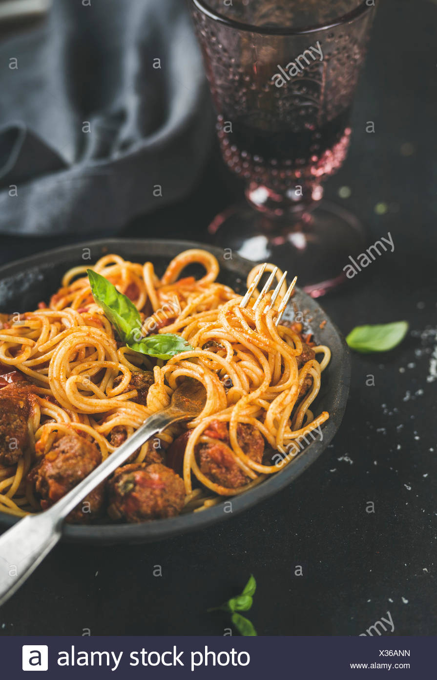 Italian pasta dinner. Spaghetti with meatballas, fresh basil leaves in dark plate and red wine in vintage glass over black background, selective focus - Stock Image