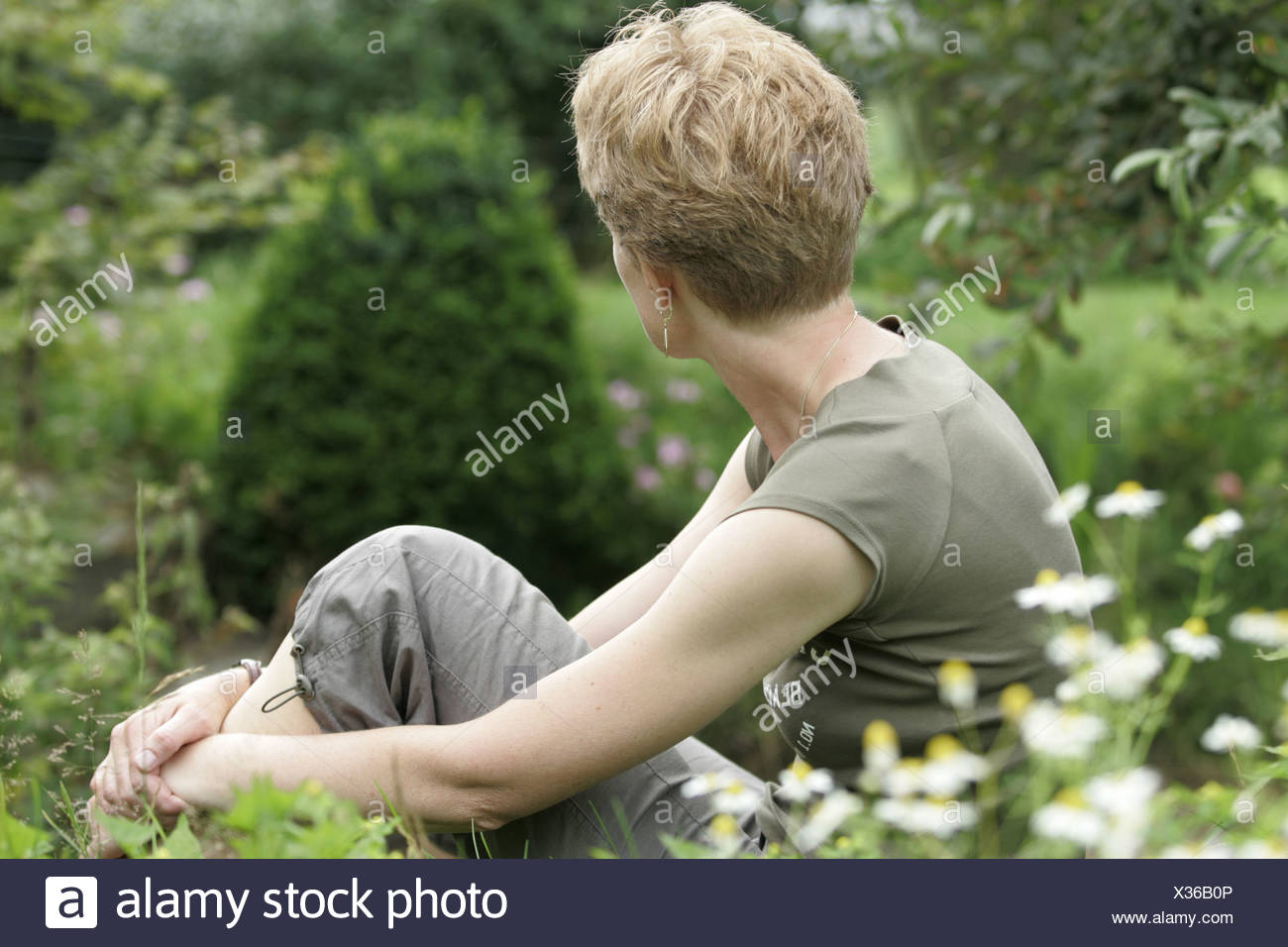 Anonymous woman alone outdoors sit in garden thinking - Stock Image