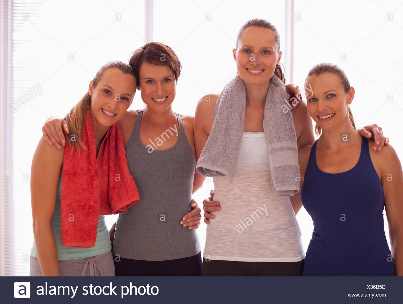 Portrait of smiling women holding yoga mats - Stock Image