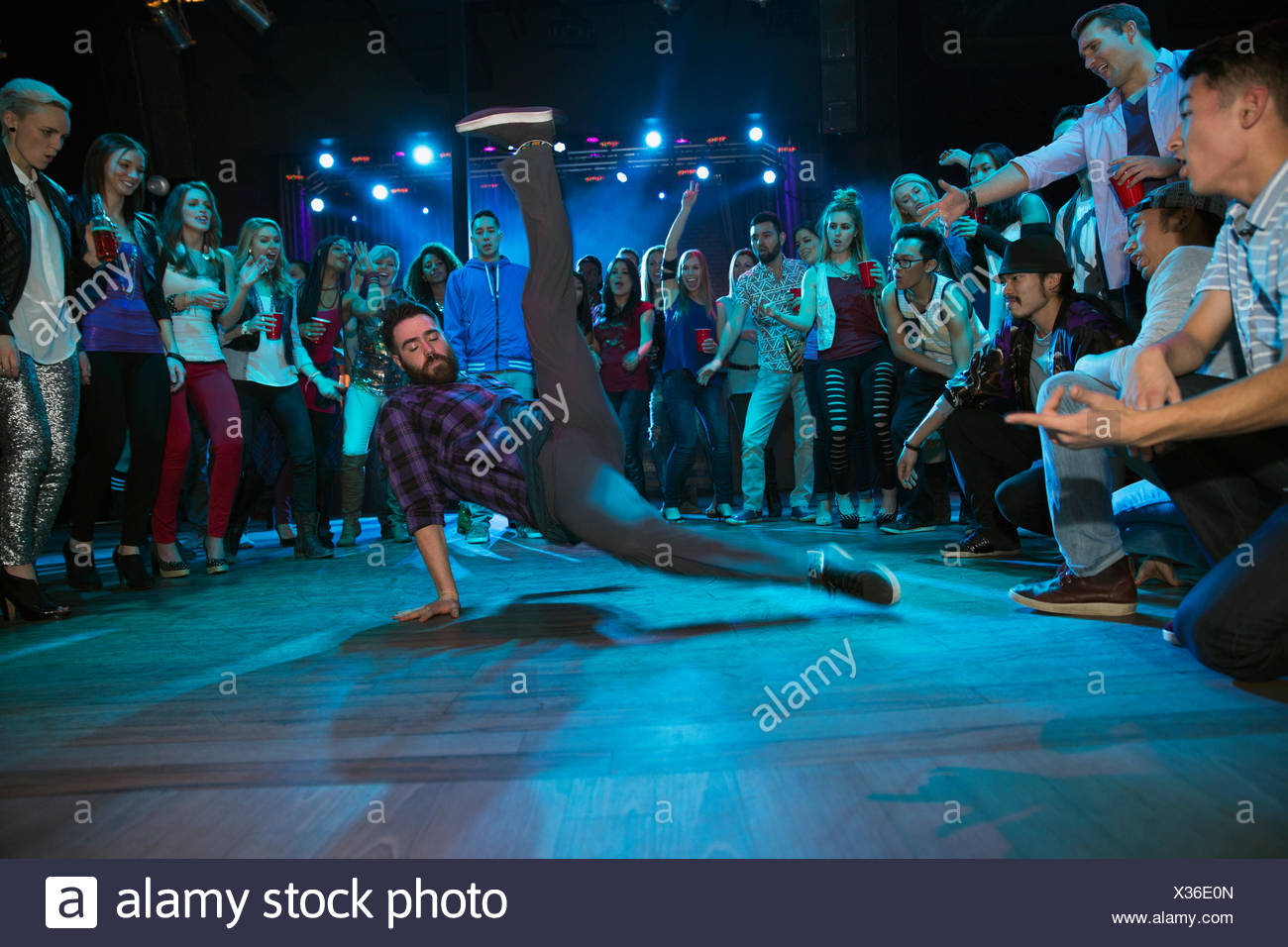 Crowd watching and cheering break dancers - Stock Image