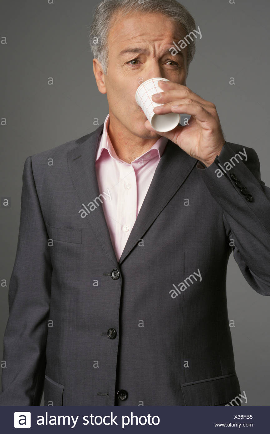 Businessman drinking a cup of water - Stock Image