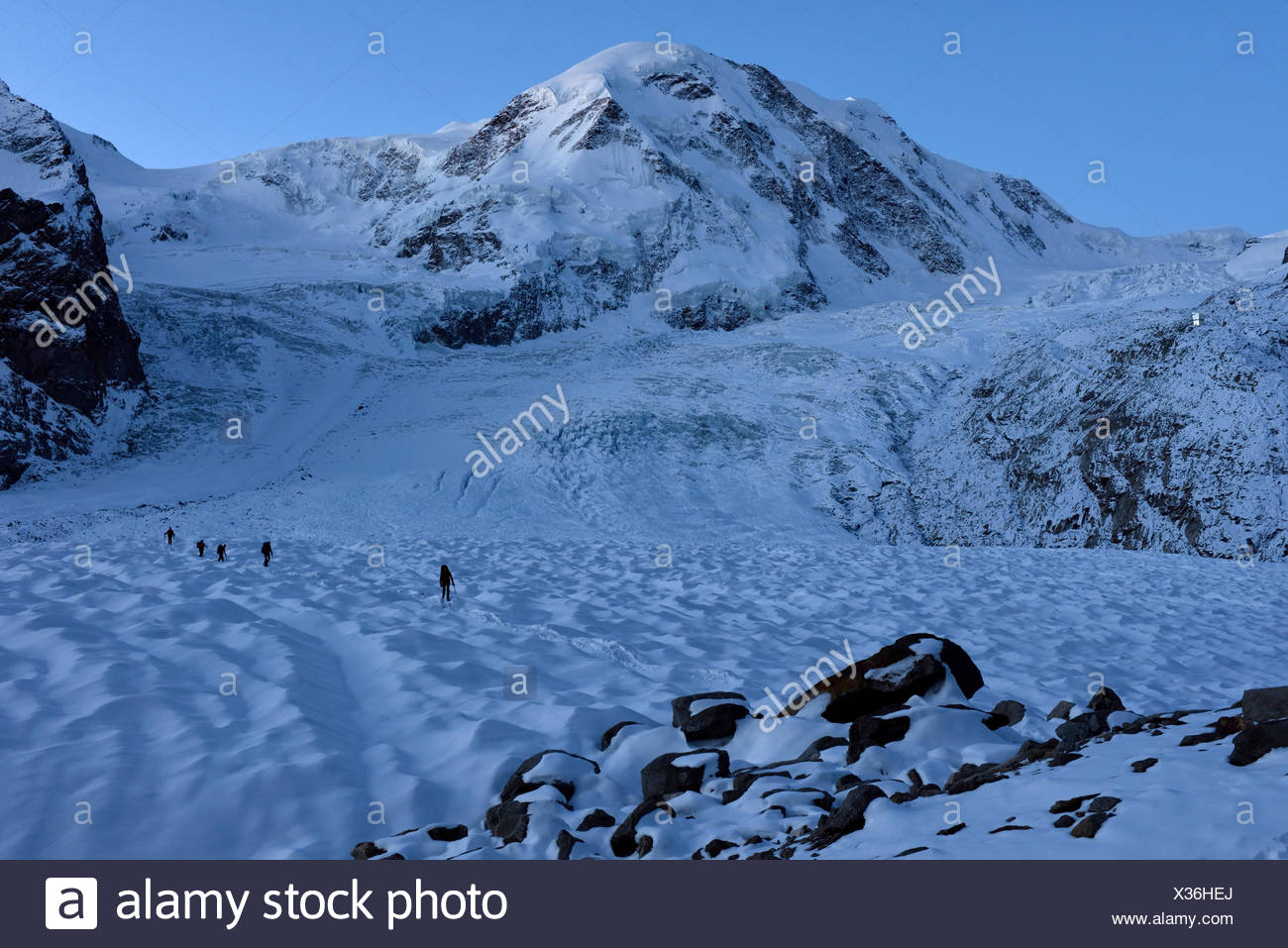 Four members of the group of Italian cave explorers return from a long day out on the ice exploring moulins in the Gorner glacier in Switzerland. The  - Stock Image