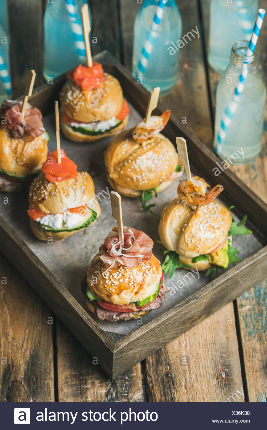 Home party food concept. Homemade burgers in wooden tray and lemonade in bottles with straws on rustic wooden table background, selective focus - Stock Image