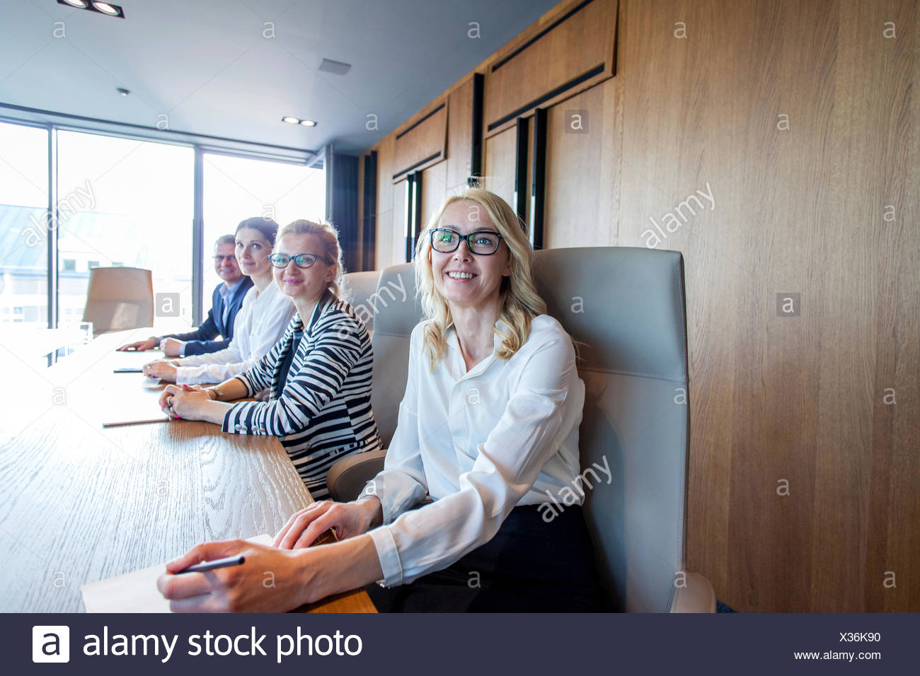 Business people sitting at conference table in board room - Stock Image