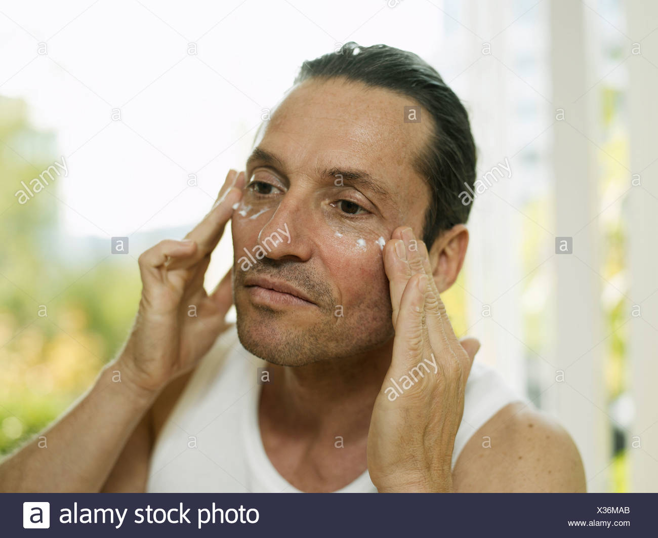 Man applying moisturizer to face - Stock Image