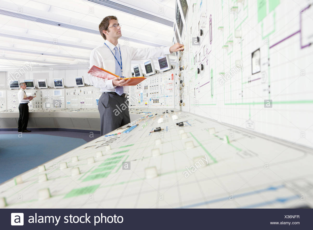 Engineer with binder looking up at computer monitor in control room of nuclear power station - Stock Image