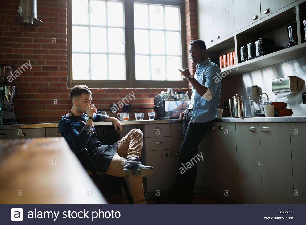 Entrepreneurial coffee roasters tasting coffee in kitchen - Stock Image