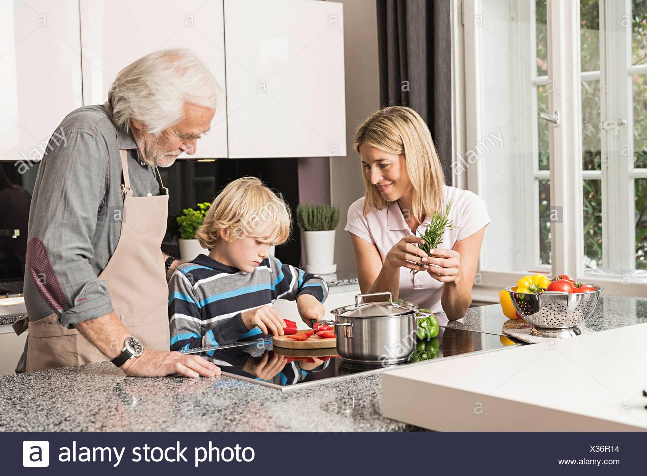 Three generation family preparing food - Stock Image