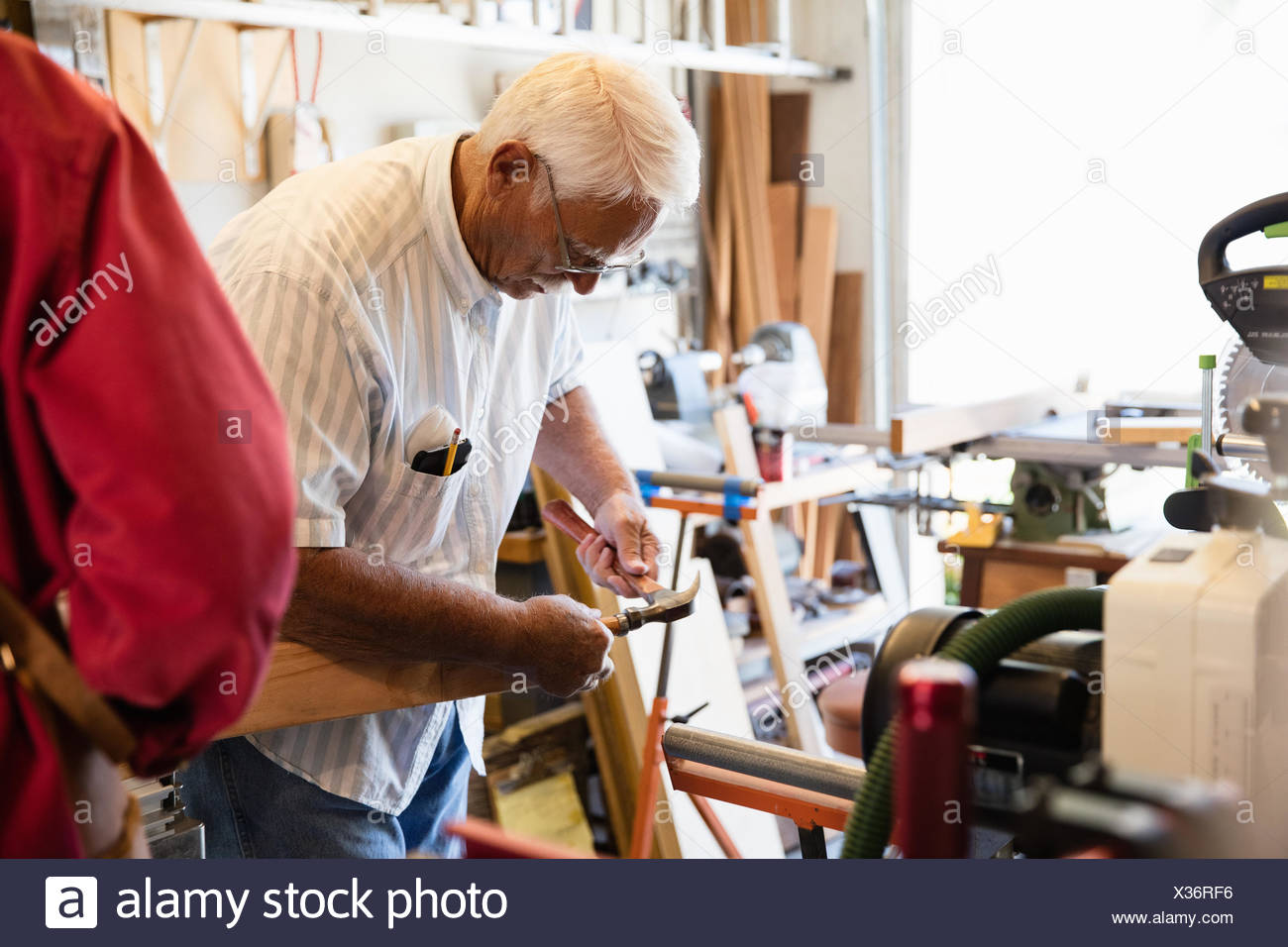 Senior man hammering woodblock in carpentry workshop - Stock Image