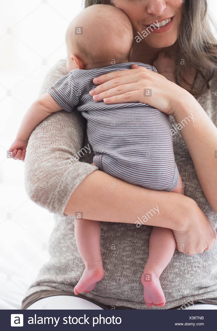 Mother holding baby boy (2-5 months) on her arm - Stock Image