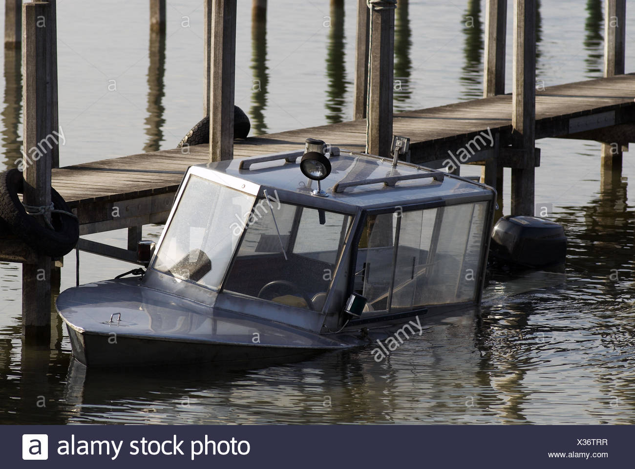 Average, landing stage, boat, wooden planks, wooden posts, automobile tyres, water, mirroring, - Stock Image