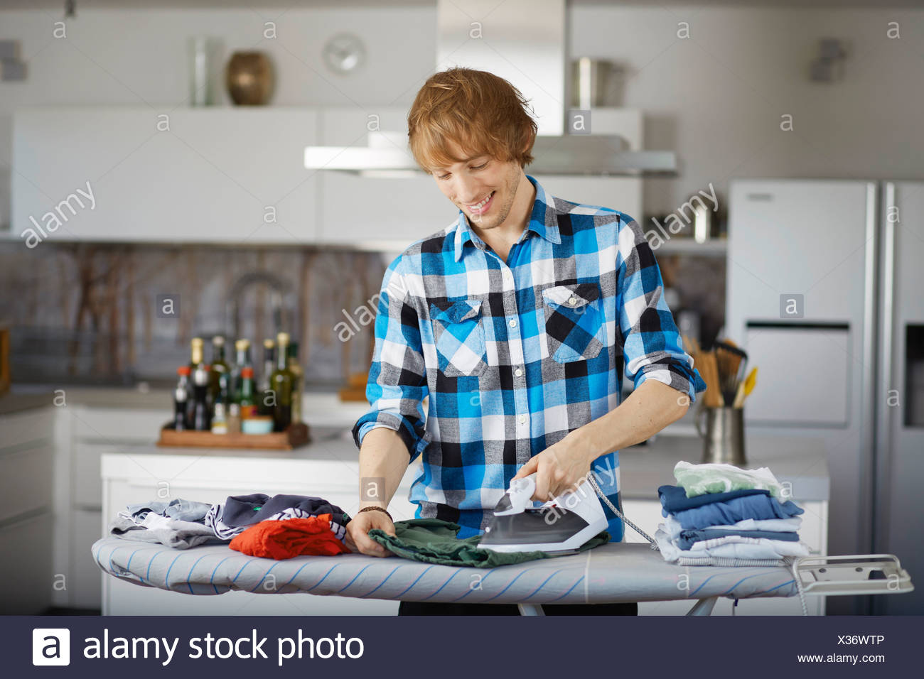 Father ironing child's clothes - Stock Image