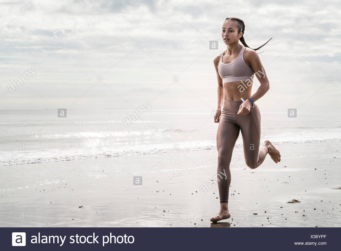 Young woman running along beach Stock Photo