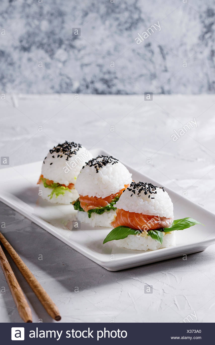 Mini rice sushi burgers with smoked salmon, green salad and sauces, black sesame served on white square plate with wooden chopsticks over gray concret - Stock Image