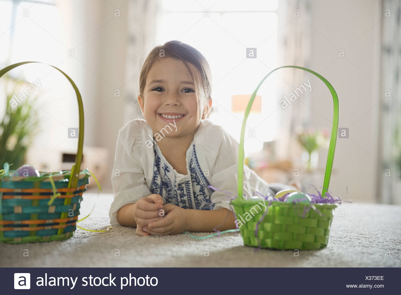 Portrait of cute girl with Easter baskets at home - Stock Image
