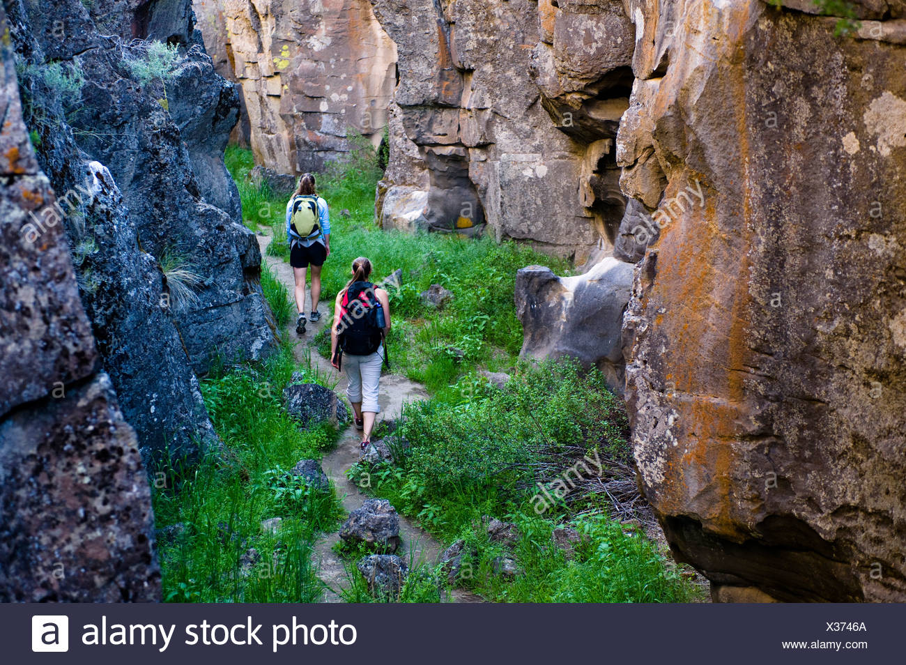 Two women hike through Crack In the Ground, a volcanic fissure near Christmas Valley, Oregon. - Stock Image
