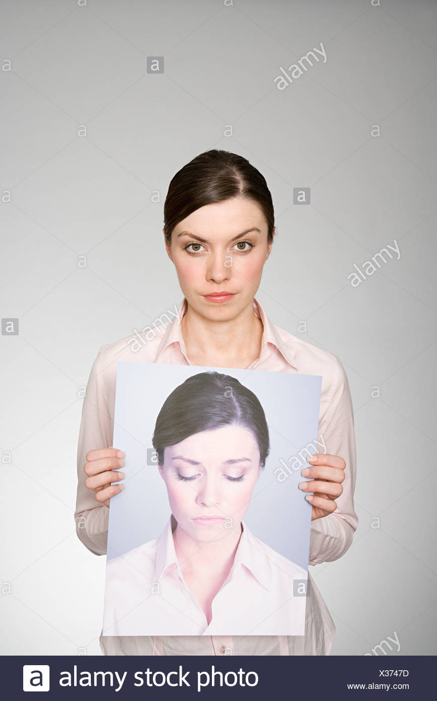 A woman holding a photograph of herself looking sad - Stock Image