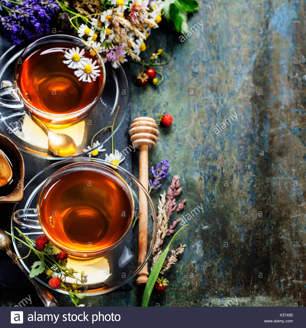 Herbal tea with honey, wild berry and flowers on wooden background - Stock Image