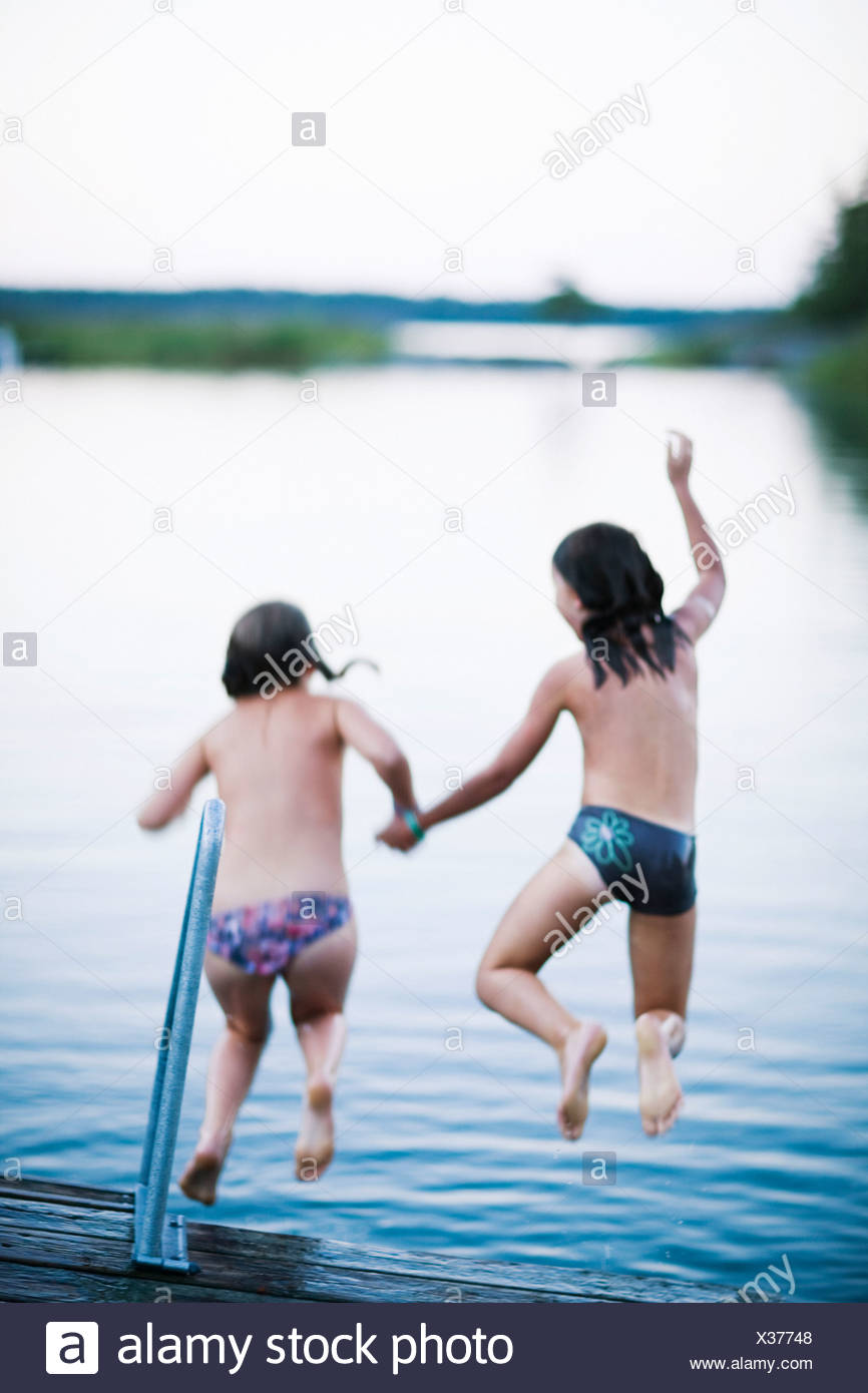 Two girls on a jetty Sweden. - Stock Image