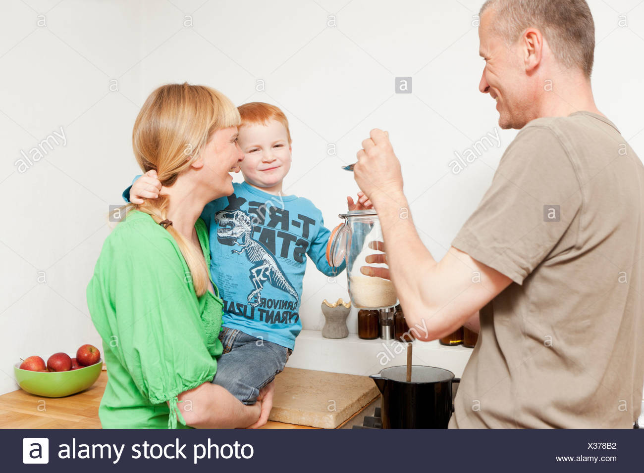 Parents feeding reluctant son in kitchen Stock Photo