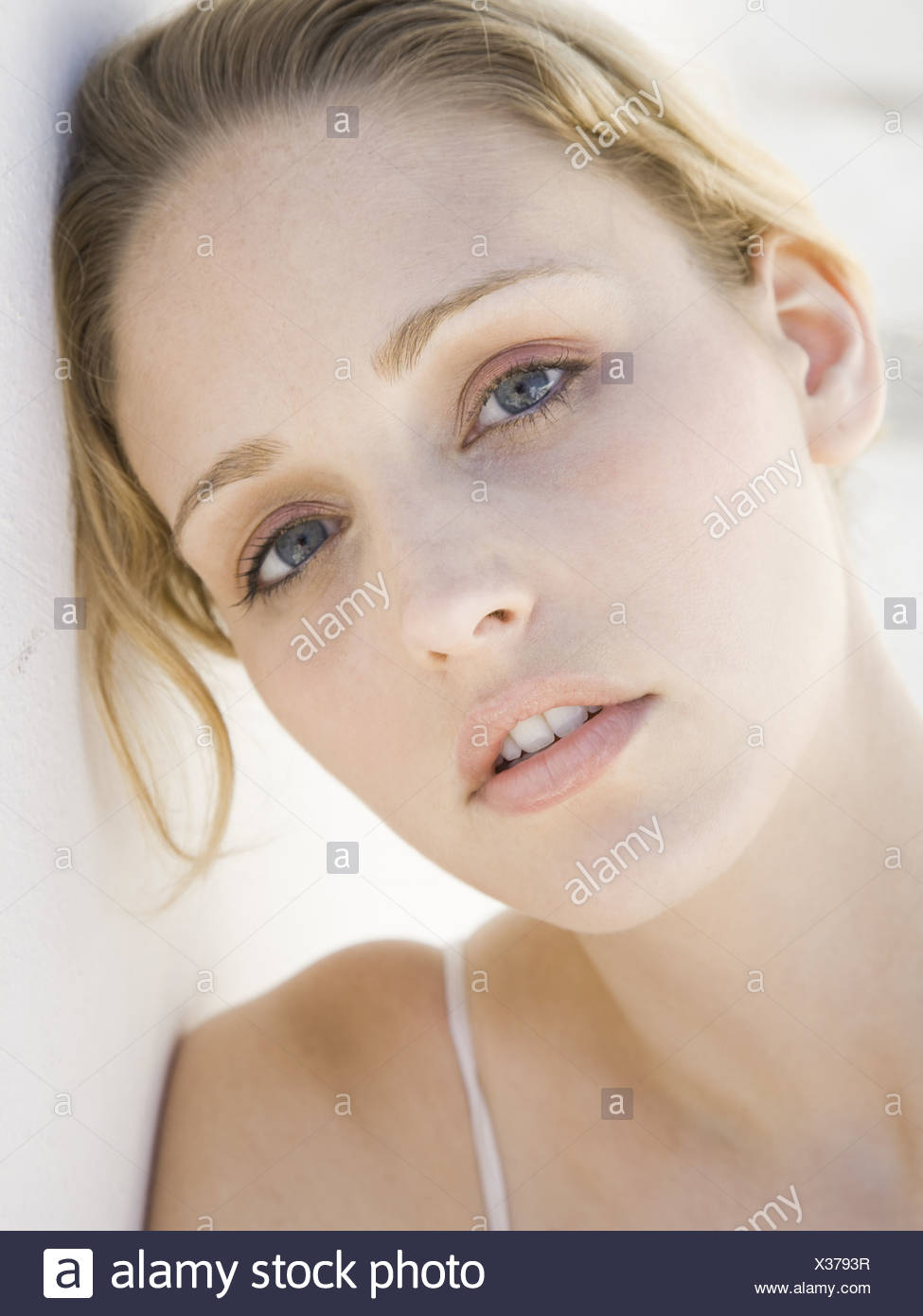 Closeup of woman leaning head on wall - Stock Image