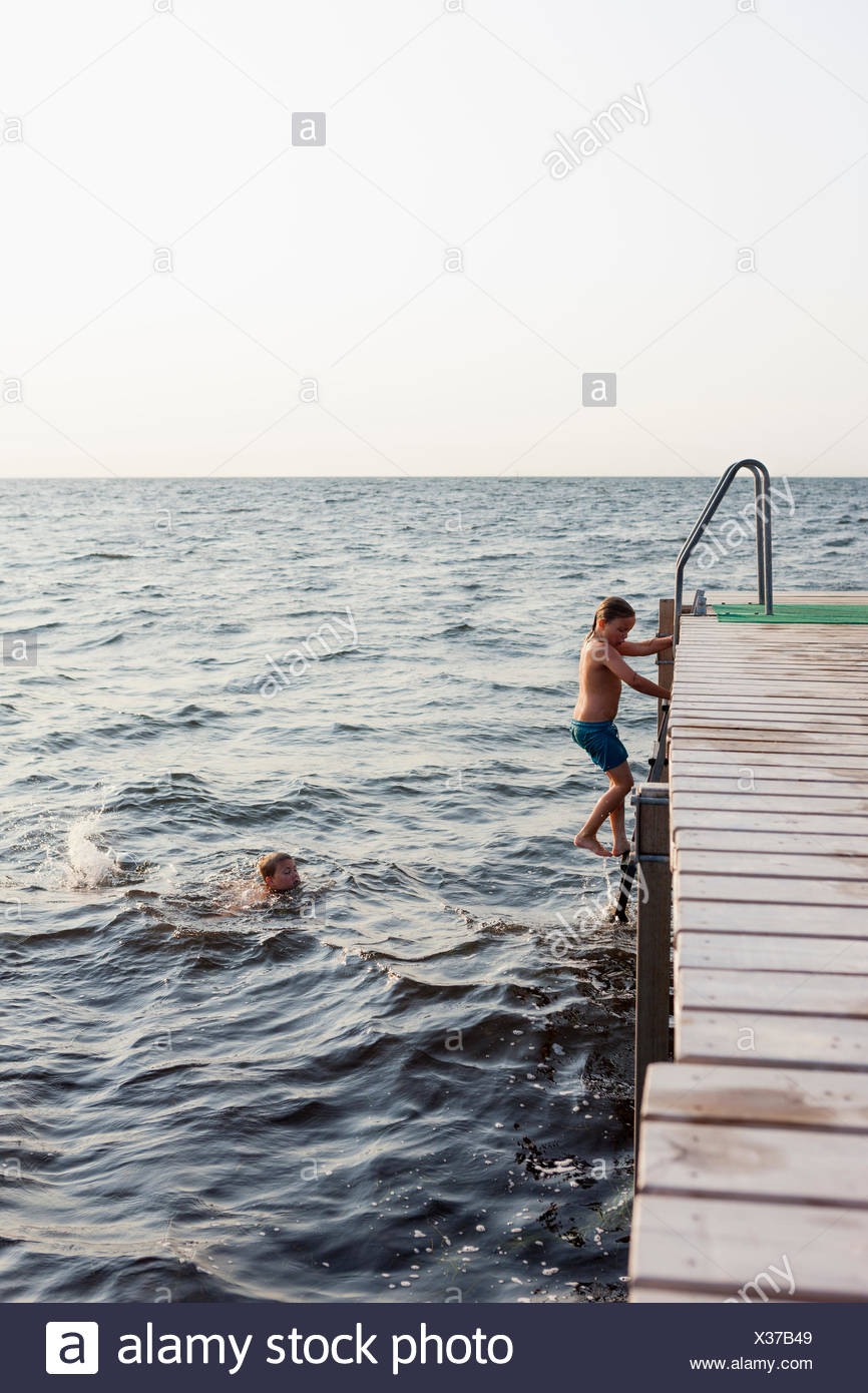 Sweden, Oland, Gronhogen, Brother (10-11) swimming while sister (6-7) climbing ladder - Stock Image