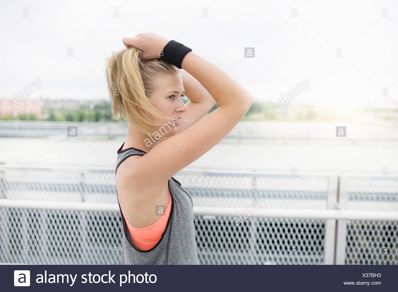 Young woman tying hair, preparing for workout, outdoors - Stock Image