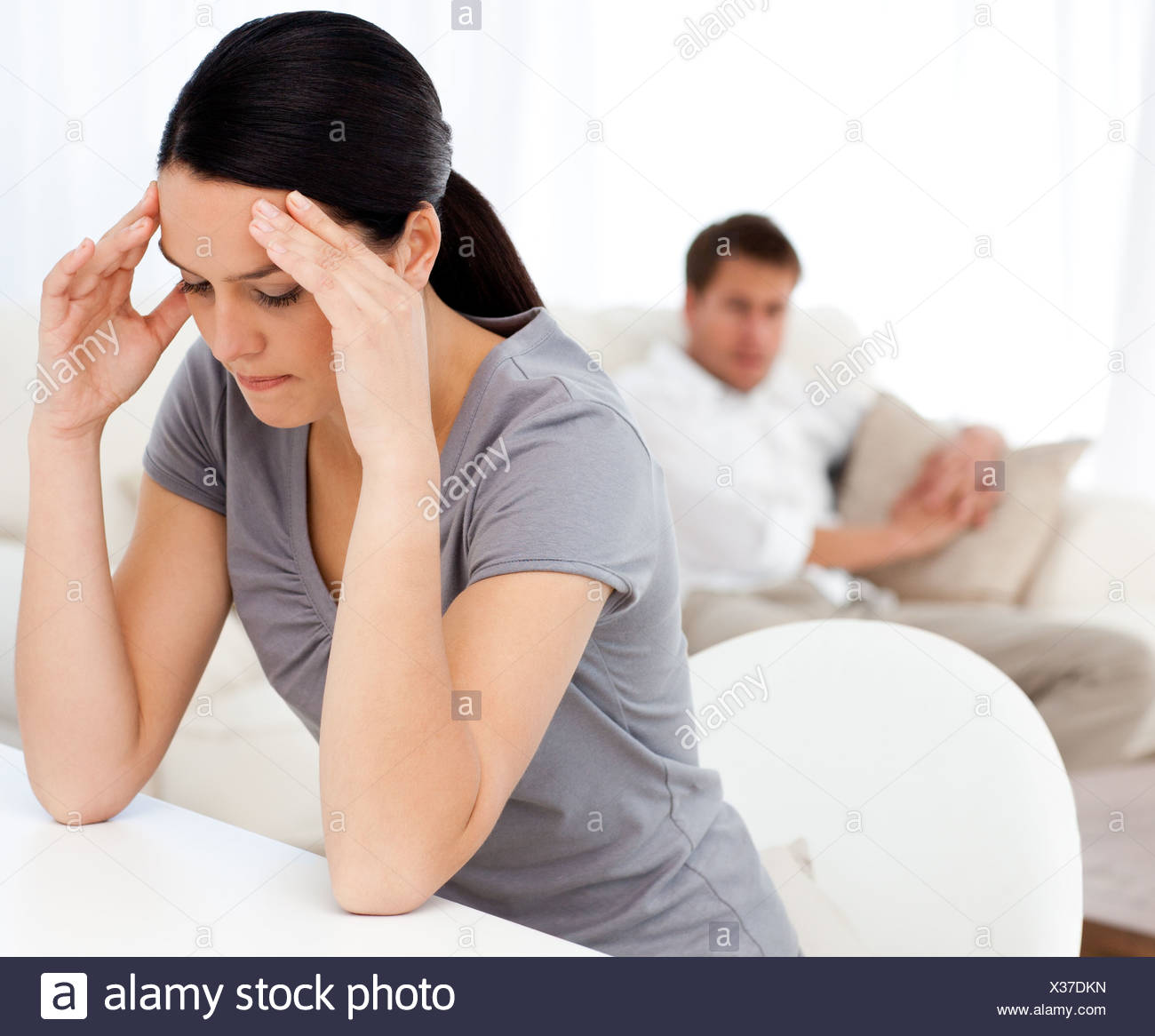 Man looking at his girlfriend having a headache sitting at a table - Stock Image