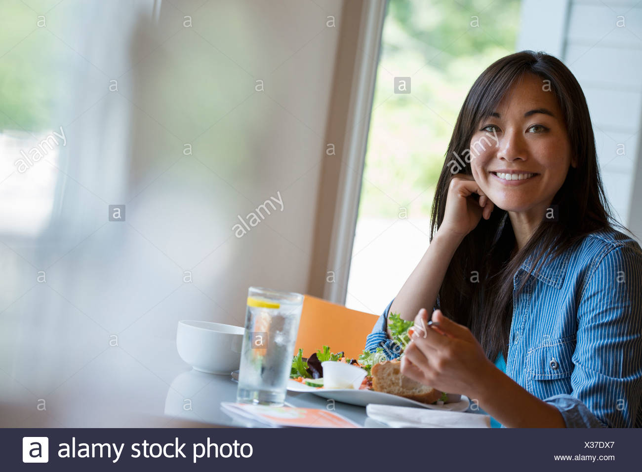 A woman seated eating in a cafe. Stock Photo