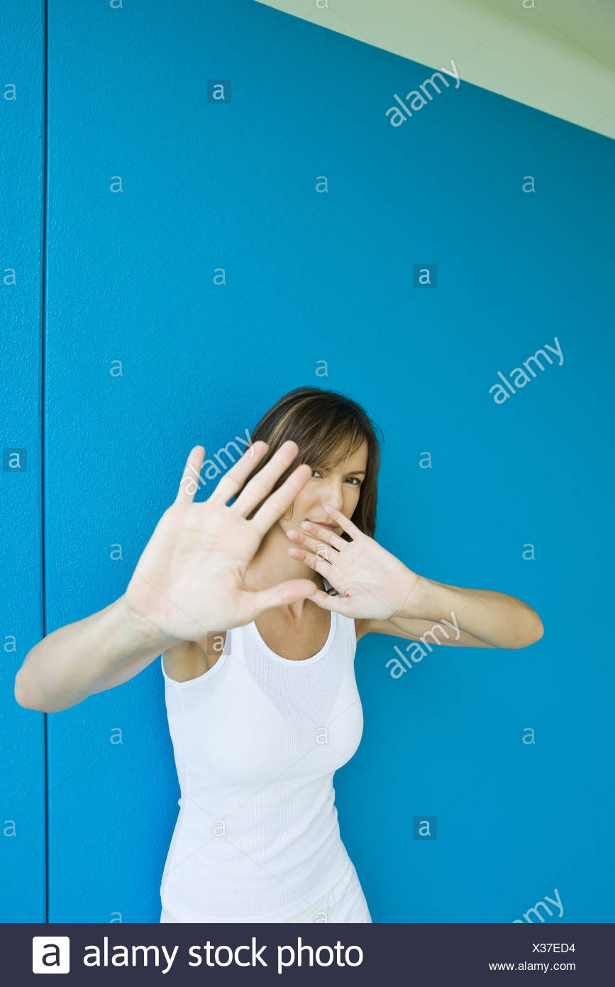 Woman holding hands in front of face, looking at camera - Stock Image