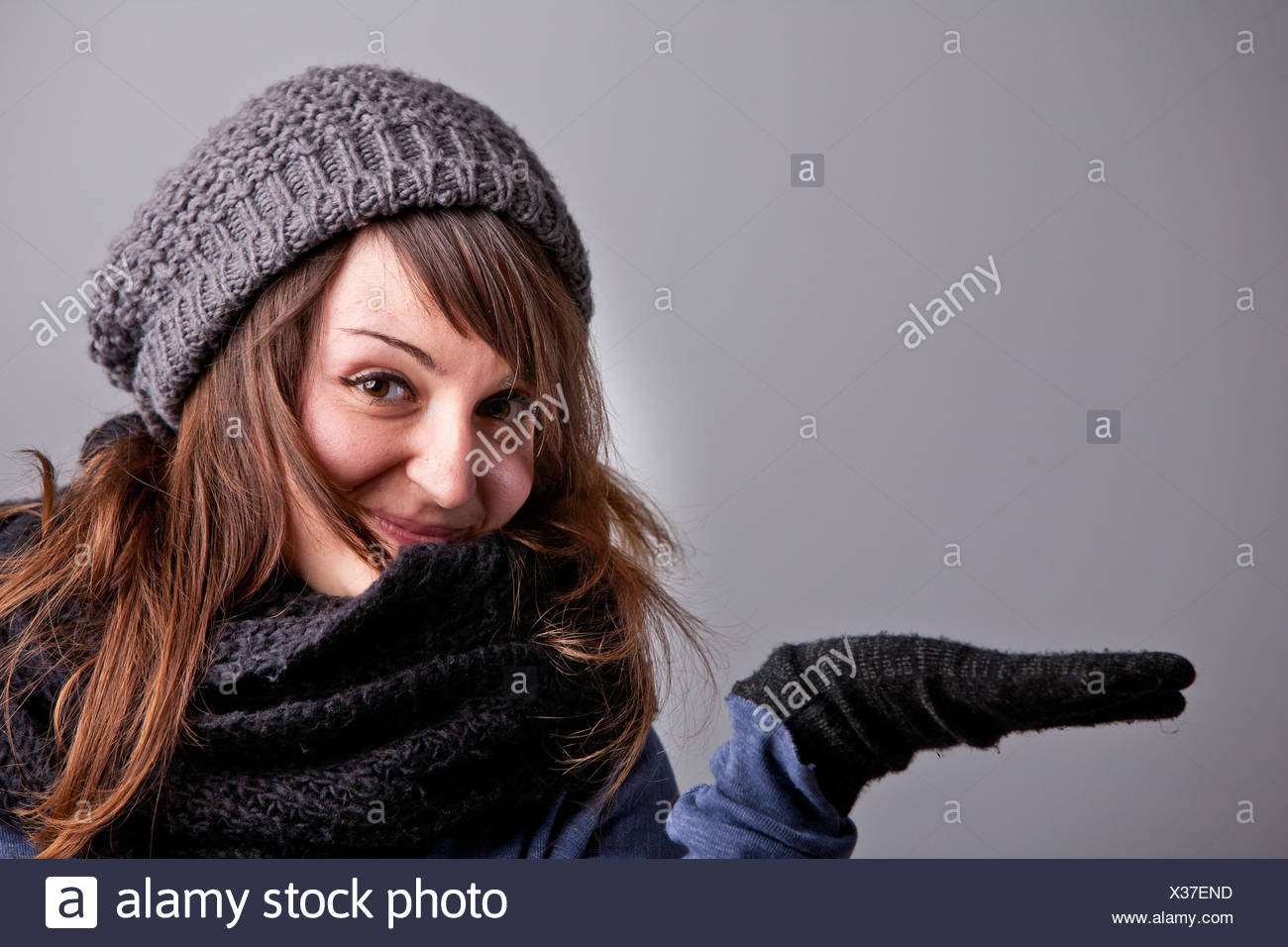 be40ac9c42140 A pretty natural smiling girl in winter clothes raising her hand to show off  your COPY SPACE