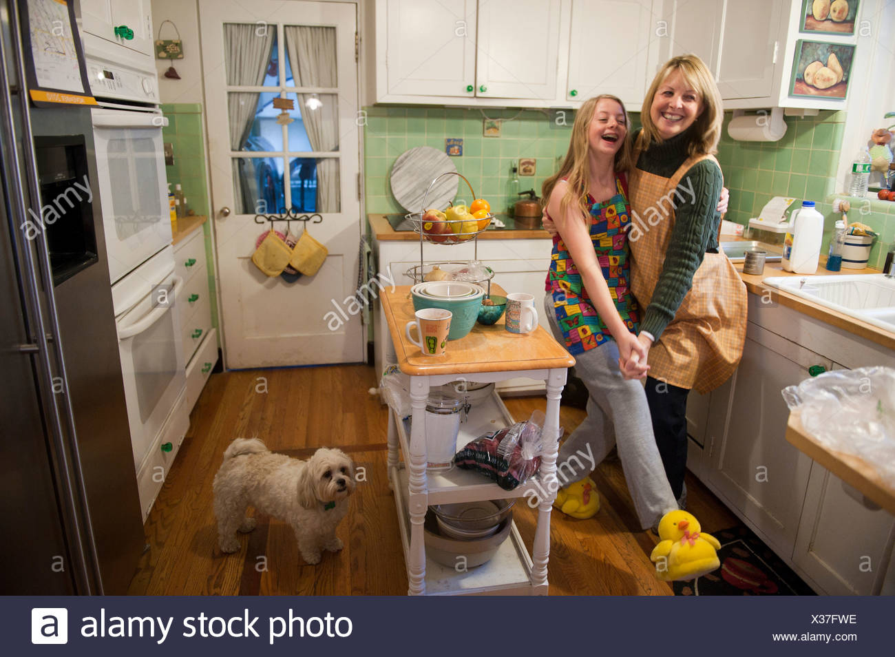 A mother and daughter playfully dance together in their kitchen