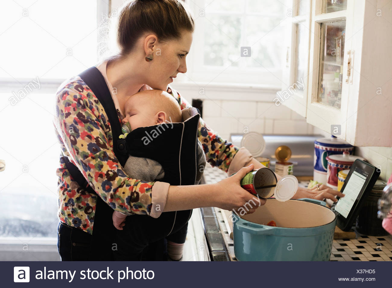 Mid adult mother with baby son in sling preparing food in kitchen Stock Photo