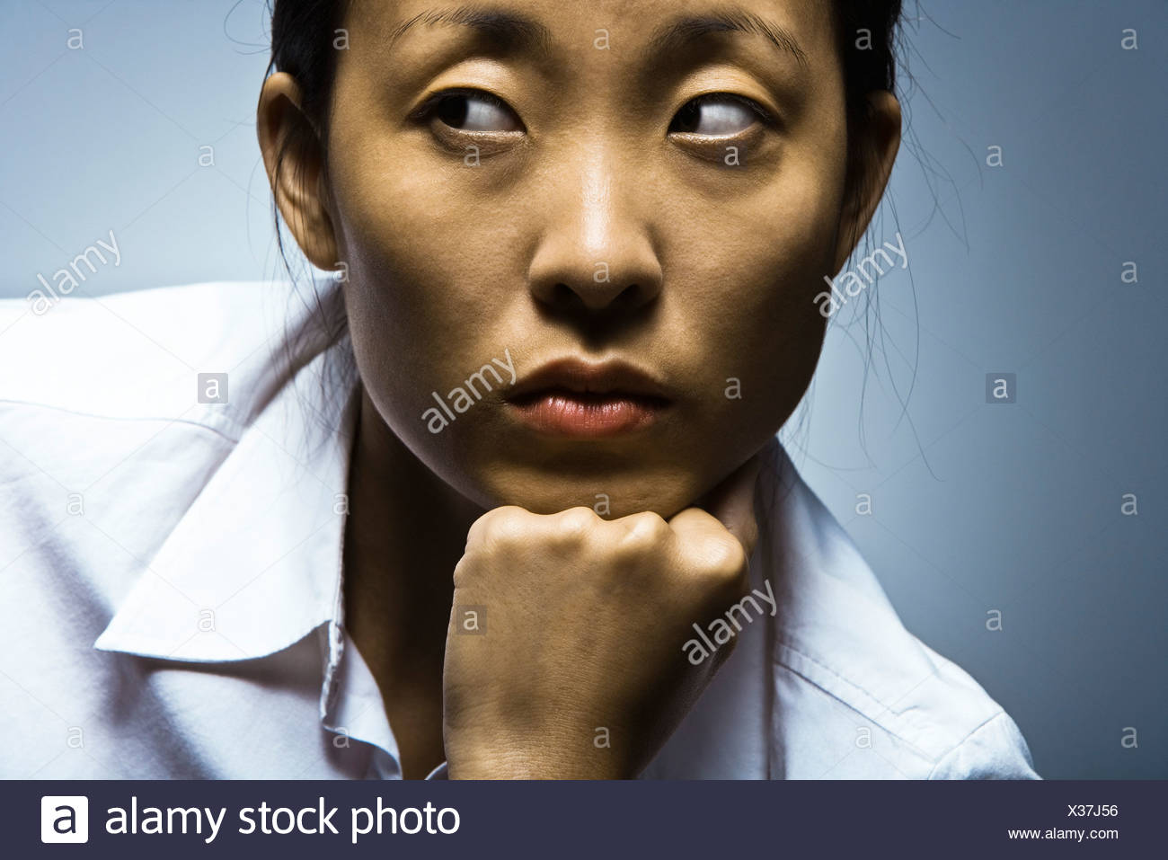 Woman glancing sideways with air of suspicion - Stock Image