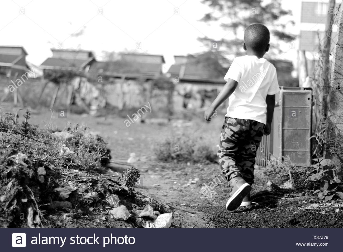 Rear View Of Boy Walking On Dirt Road - Stock Image
