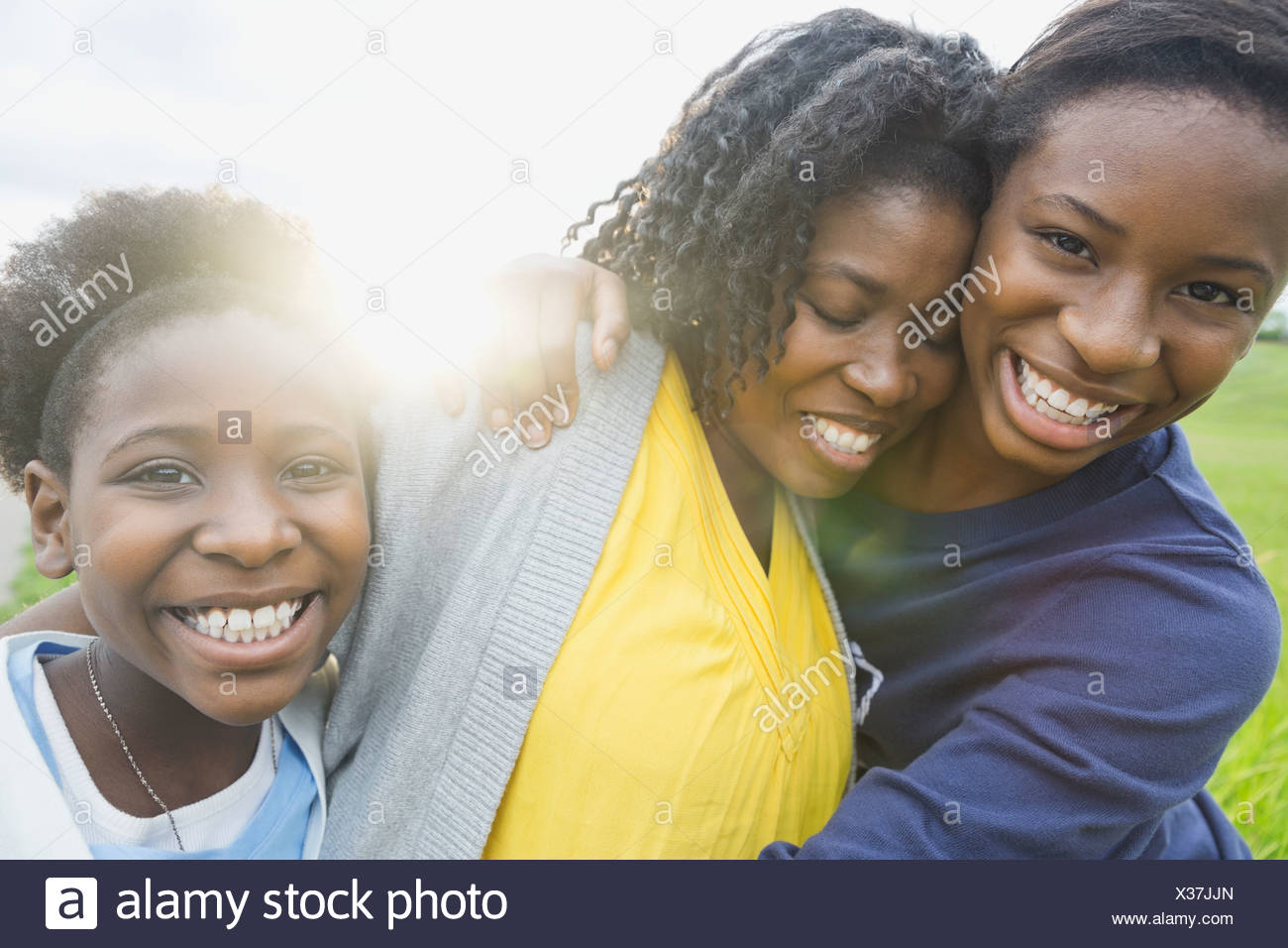 Portrait of happy daughters embracing mother outdoors - Stock Image