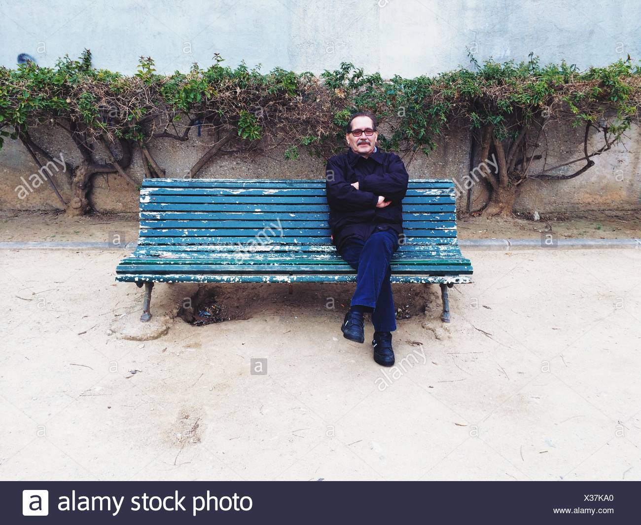 Full Length Of Mature Man Relaxing On Park Bench - Stock Image