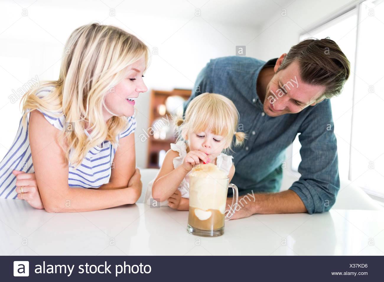 Girl (2-3) drinking milkshake with parents at home - Stock Image