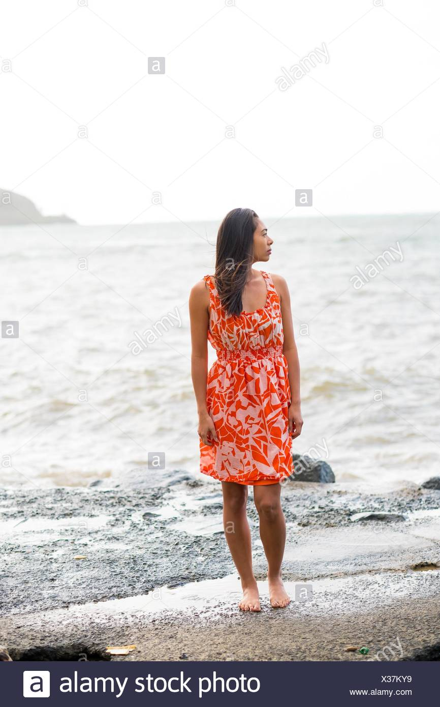 Lifestyle portrait of an attractive Hawaiian woman wearing a flower dress at Kahana Bay on Oahu Hawaii. - Stock Image