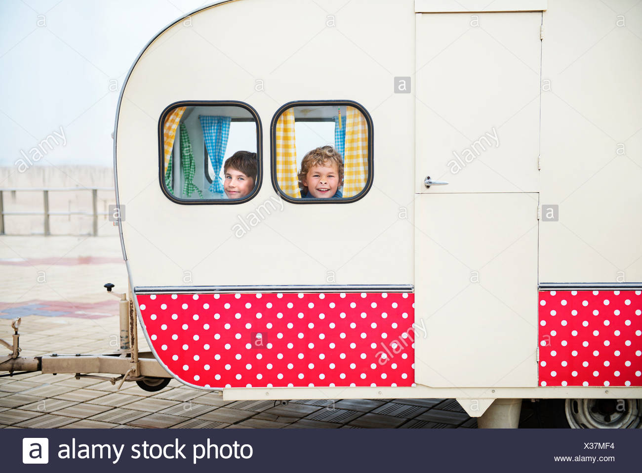 Boys looking through caravan windows, portrait - Stock Image