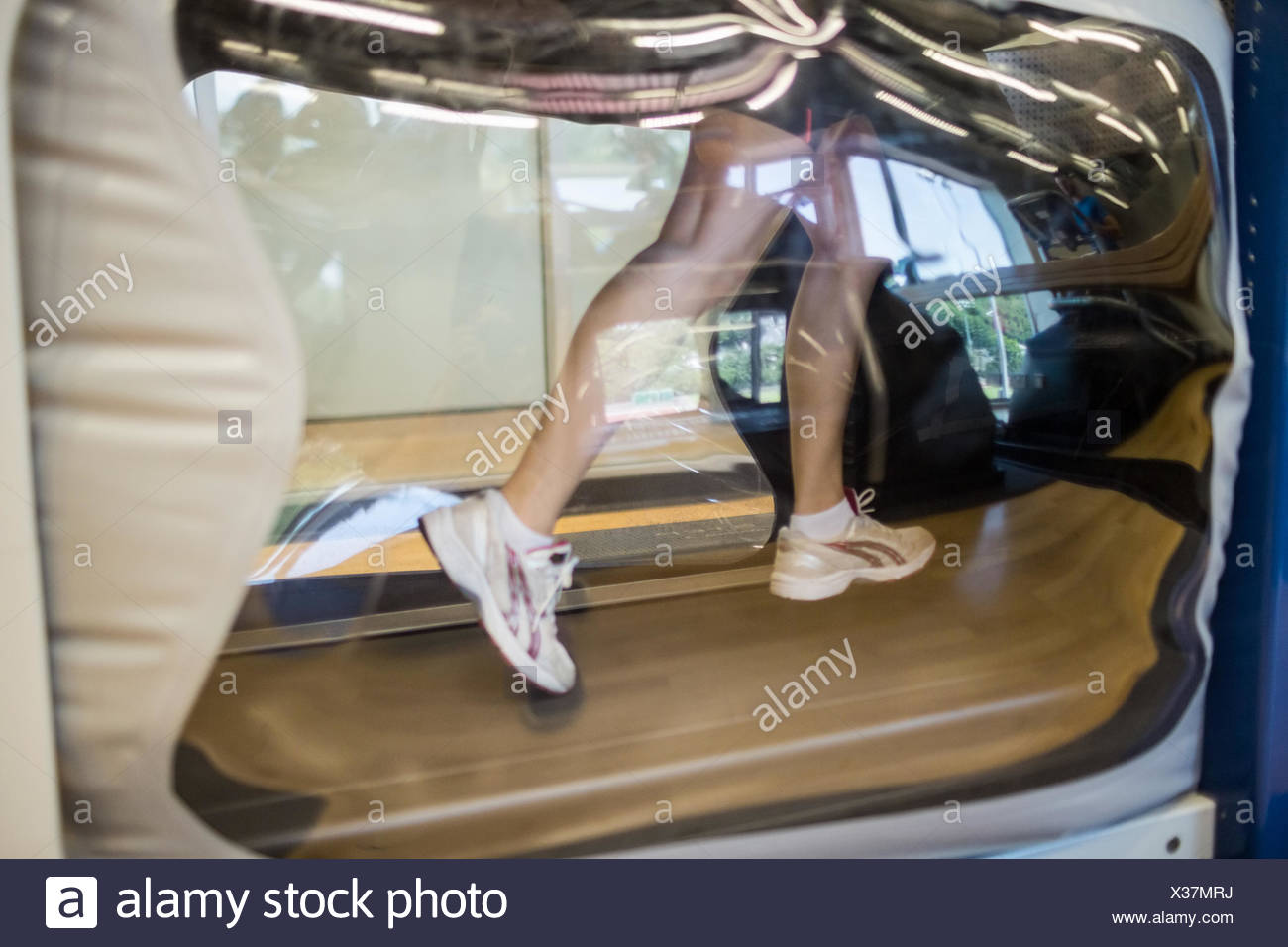 Athlete working out on an anti gravity treadmill - Stock Image