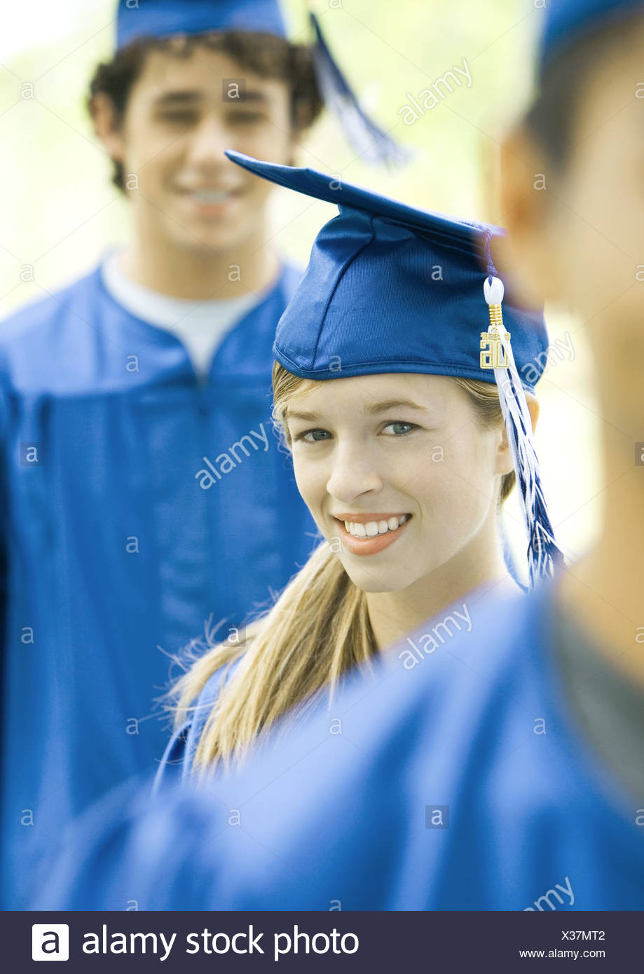 Graduates in line, smiling, focus on young woman - Stock Image