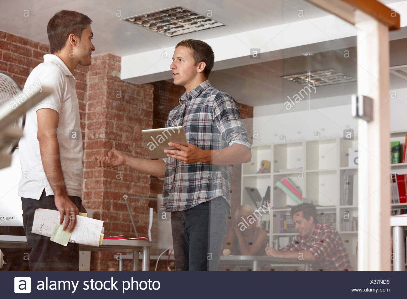 Male colleagues with digital tablet in modern office - Stock Image