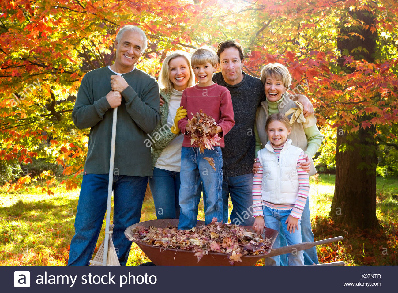 Three generation family doing yard work together in autumn - Stock Image
