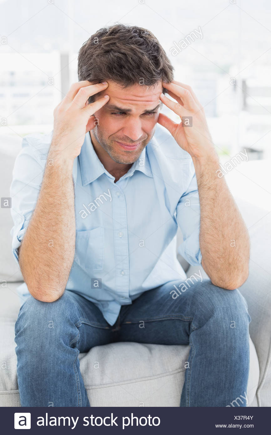 Grimacing man sitting on the couch with a headache - Stock Image